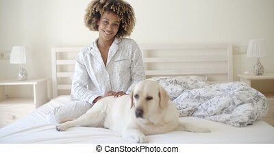Woman And Her Dog Resting In Bed