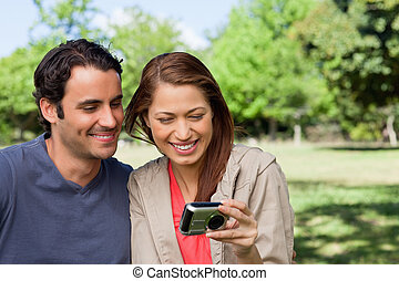 Woman and her friend looking at pictures on a camera