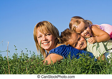 Woman and her kids playing outdoors - Woman and kids playing...