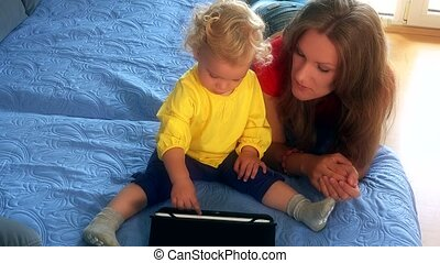 woman and her little daughter girl playing on bed with tablet computer