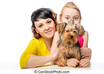 woman and her little daughter posing with a dog on a white background
