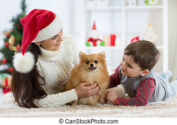 Woman and her son celebrating christmas with furry friend. Mother and kid with terrier dog. Pretty child boy with puppy at x-mas tree.