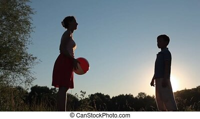 woman and her son plays with ball in park