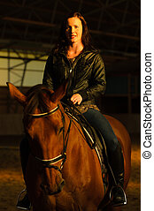 Woman and horse in indoor arena, woman looks toward camera, vertical format