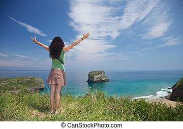 woman and islet in Asturias - beach of Ballota near to...