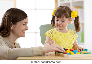 Woman and kid girl playing logical toys at home