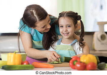 Woman and kid girl preparing a vegetables salad in the kitchen