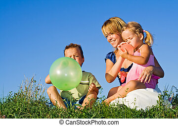 Woman and kids playing with balloons