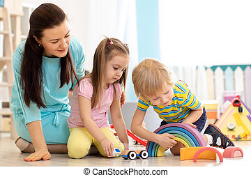 Woman and kids playing with wooden blocks sitting on the floor