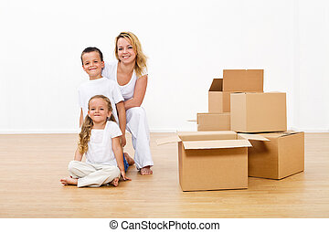 Woman and kids unpacking in their new home
