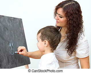 Woman and little boy drawing on board