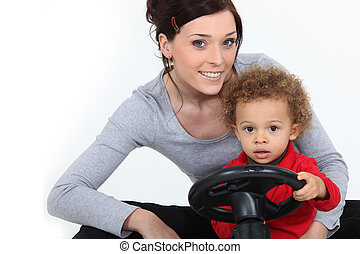 Woman and little boy on a toy car