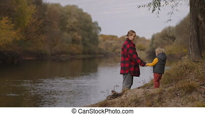 woman and little child are standing on coast of river at ...