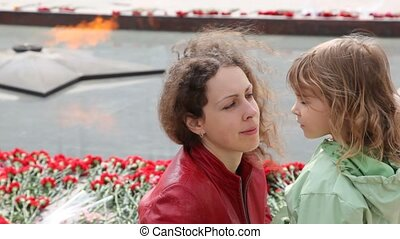 woman and little daughter against eternal fire in Moscow