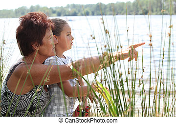 Woman and little girl at a riverside