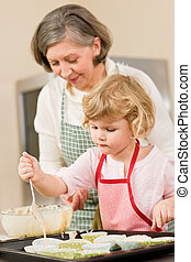 Woman and little girl baking cupcakes together - Woman and...