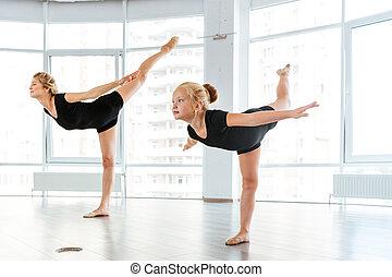 Woman and little girl ballerina dancing in ballet school