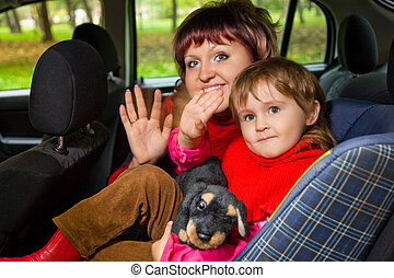 woman and  little girl  Greeting to wave hands in car in park