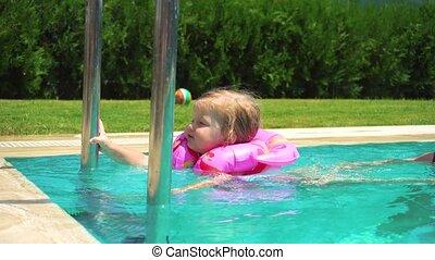 Woman and little girl having fun in swimming pool