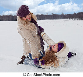 Woman and little girl having fun in the snow