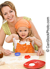 Woman and little girl making cookies