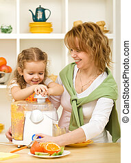 Woman and little girl making fruit juice
