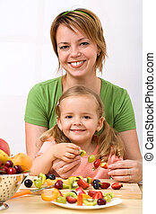 Woman and little girl making fruit kebab