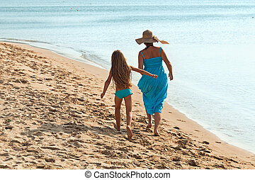 Woman and little girl on a morning walk by the sea