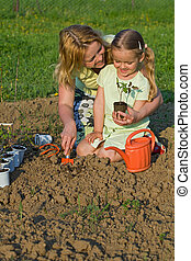 Woman and little girl planting seedlings together