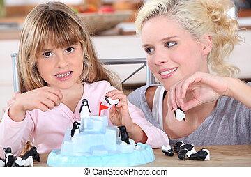 Woman and little girl playing with toys
