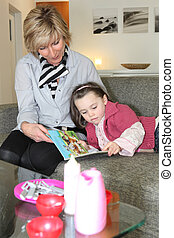 Woman and little girl reading a book