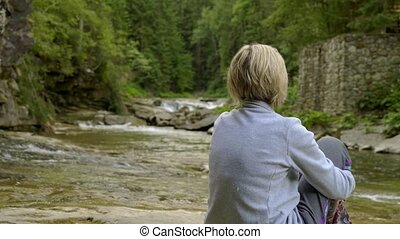 Woman and little girl sitting on rocks at mountain river -...