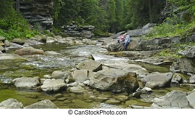 Woman and little girl sitting on rocks at mountain river