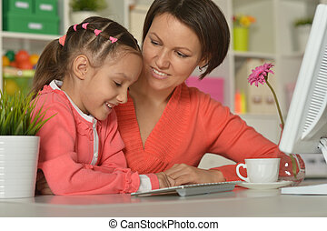 woman and little girl using computer