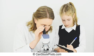 Woman and little girl using microscope in laboratory.