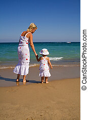 Woman and her little girl walking by the sea in the summer, holding hands, dressed alike