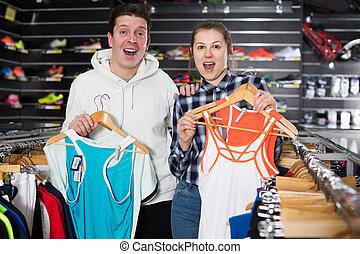 Woman and man are choosing tennis uniform