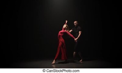 Woman and man are dancing with supports on the black background under spotlight in a dark studio. Slow motion