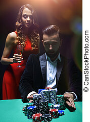 woman and man at the poker table with chips and drinks