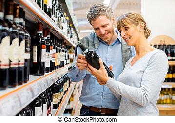Woman and man buying wine in supermarket