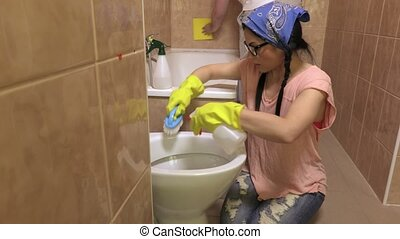 Woman and man cleaning bathroom