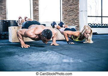 Woman and man doing push ups