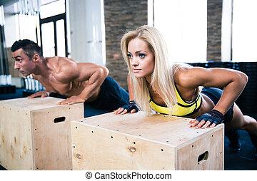 Woman and man doing push ups at gym