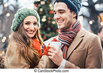Woman and man drinking mulled wine on Christmas Market