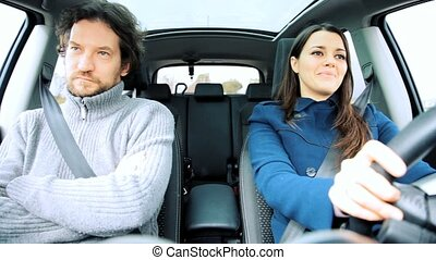 Woman and man driving looking into