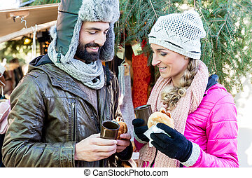 Woman and man eating and drinking on Christmas market