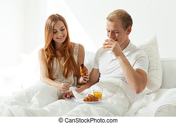Woman and man eating breakfast in bed
