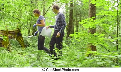 Woman and man ecologists taking samples of a soil - Man and...