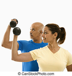 Smiling mid adult multiethnic man and woman exercising with dumbbells doing bicep curls.