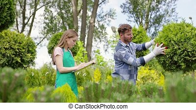 Woman and man exploring plants in botanic garden - Young...